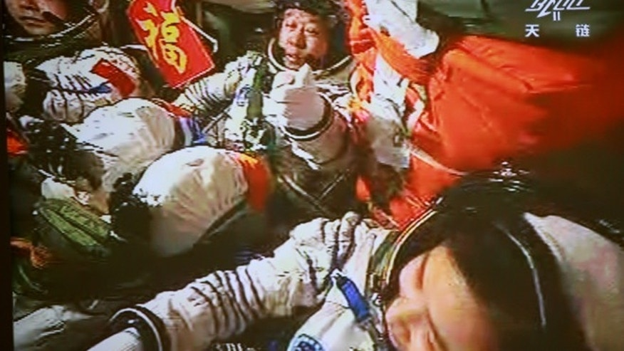 June 18, 2012: In this image made off the monitor screen at the Beijing Aerospace Flight Control Center, China&#39&#x3b;s astronauts Jing Haipeng, center, Liu Wang, left, and Liu Yang sit inside the Shenzhou-9 manned spacecraft while docking with the Tiangong-1 space lab module, 213 miles above Earth.