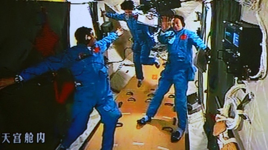 June 18, 2012: In this image made off the monitor screen at the Beijing Aerospace Flight Control Center, Chinese astronaut Liu Wang, left, tries to help his female colleague Liu Yang move forward as their commander Jing Haipeng waves in the orbiting Tiangong-1 lab module.