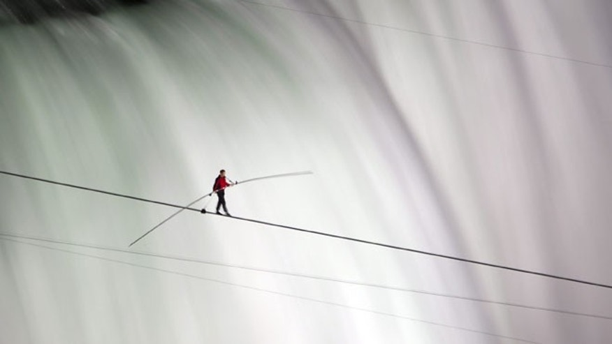 June 15, 2012: Nik Wallenda walks over Niagara Falls on a tightrope in Niagara Falls, Ontario. Wallenda has finished his attempt to become the first person to walk on a tightrope 1,800 feet across the mist-fogged brink of roaring Niagara Falls.