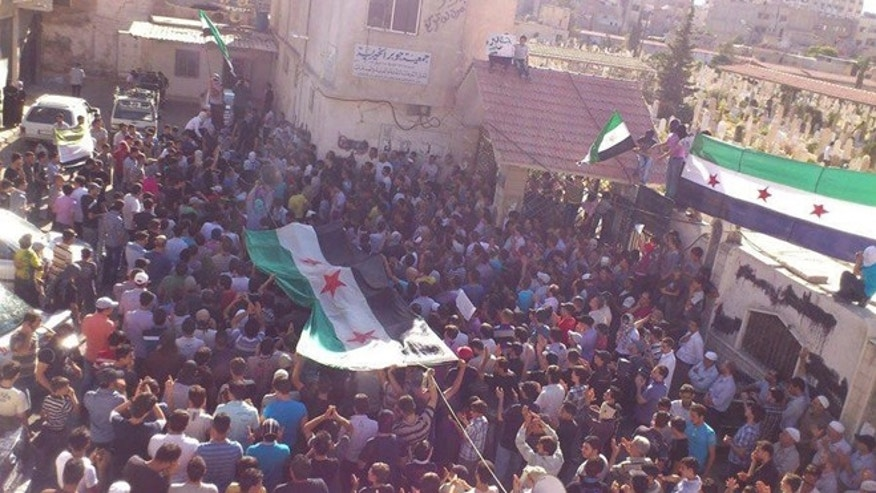 June 18: Residents gather during the funeral of Hussein Omish, whom protesters say was killed by forces loyal to Syria's President Bashar al-Assad.