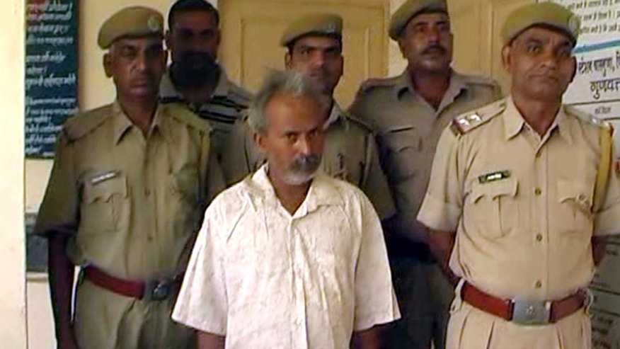June 18, 2012: In this image made off video footage, Indian marble miner Oghad Singh, center, stands with policemen after they placed Singh in custody in Charbhuja, Rajasthan state, India.