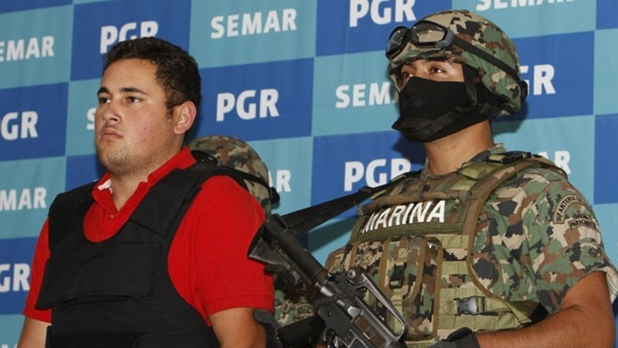 June 21, 2012: A Mexican marine escorts Jesus Alfredo Guzman Salazar, left, during his presentation to the media in Mexico City.