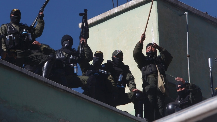 June 22, 2012: Police demanding salary increases shout slogans on the roof of a police internal affairs building that was sacked and its content burned, in La Paz, Bolivia.