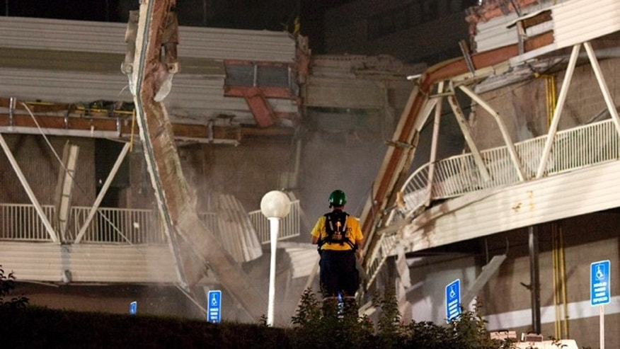 June 26, 2012: A rescue worker watches as a demolition crane as it tears into part of the Algo Centre Mall, in Elliot Lake, Ontario.
