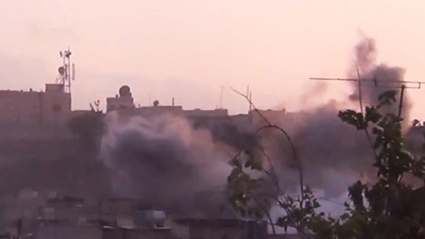 June 26, 2012: In this image made from amateur video released by the Shaam News Network smoke rises from buildings following purported shelling in Homs, Syria.