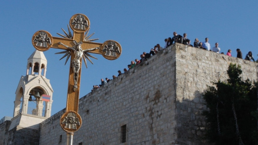 Dec, 24, 2012:This file photo shows a cross in front of the Church of Nativity, traditionally believed by Christians to be the birthplace of Jesus Christ, during a Christmas parade in the West Bank town of Bethlehem.