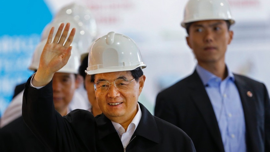 June 30, 2012: Chinese President Hu Jintao waves to reporters during a visit to the Kai Tak Cruise Terminal Building  in Hong Kong.