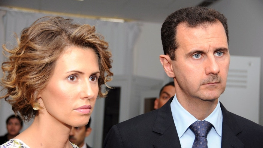 July 13, 2012: In this file photo, Syrian President Bashar Assad, left, and his wife Asma Assad, listen to explanations as they visit a technology plant in Tunis.