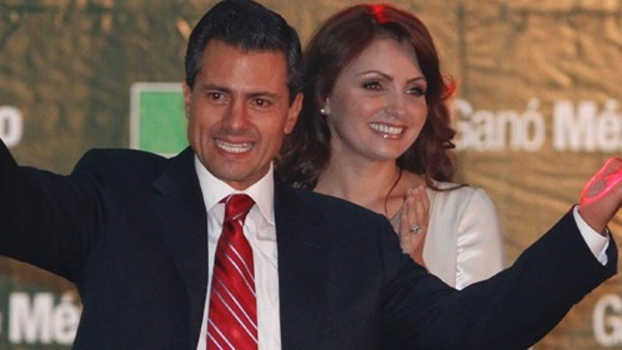 Presidential candidate Enrique Pena Nieto gestures to supporters next to his wife Angelica Rivera at his party's headquarters in Mexico City, early Monday, July 2, 2012.   Mexico's old guard sailed back into power after a 12-year hiatus Sunday as the official preliminary vote count handed a victory to Pena Nieto, whose party was long accused of ruling the country through corruption and patronage.(AP Photo/Marco Ugarte)