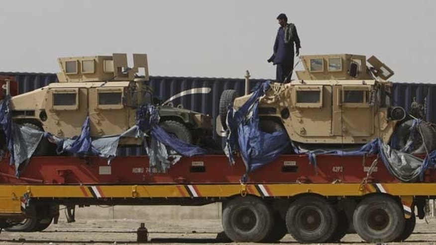 July 4, 2012: A driver stands on top of a truck carrying NATO Humvees at a terminal in the Pakistani-Afghan border, in Chaman, Pakistan.