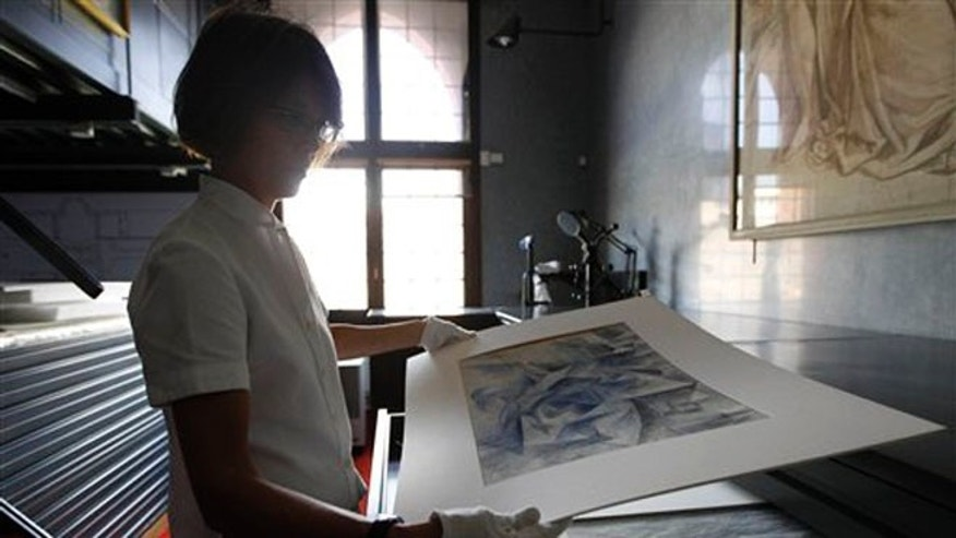 July 6, 2012: Francesca Rossi, curator in charge of the Sforzesco Castle drawings collection, looks at a work by Umberto Boccioni, in the same room where sketches by mannerist painter Simone Peterzano are preserved, in Milan.
