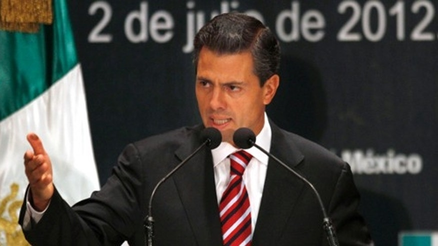Enrique Pena Nieto, candidate of the Institutional Revolutionary Party (PRI) and apparent winner of Mexico's presidential election, speaks during a news conference in Mexico City, Monday, July 2, 2012. The party that ruled Mexico with a tight grip for most of the last century has sailed back into power, promising a government that will be modern, responsible and open to criticism. (AP Photo/Marco Ugarte)