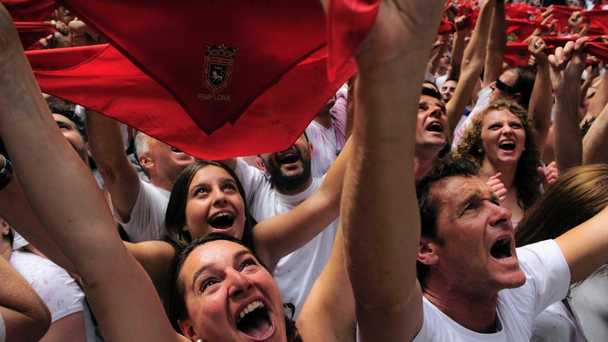 "Revelers hold up traditional red neckties as tens of thousands of people packed Pamplona's main square in Pamplona, northern Spain, Friday, July 6, 2012 to celebrate the start of Spain's most famous bull-running festival with the annual launch of the ""chupinazo"" rocket. Perhaps best glorified by Ernest Hemingway's 1926 novel ""The Sun Also Rises,"" the San Fermin festival is known around the world for the daily running of the bulls. (AP Photo/Alvaro Barrientos)"