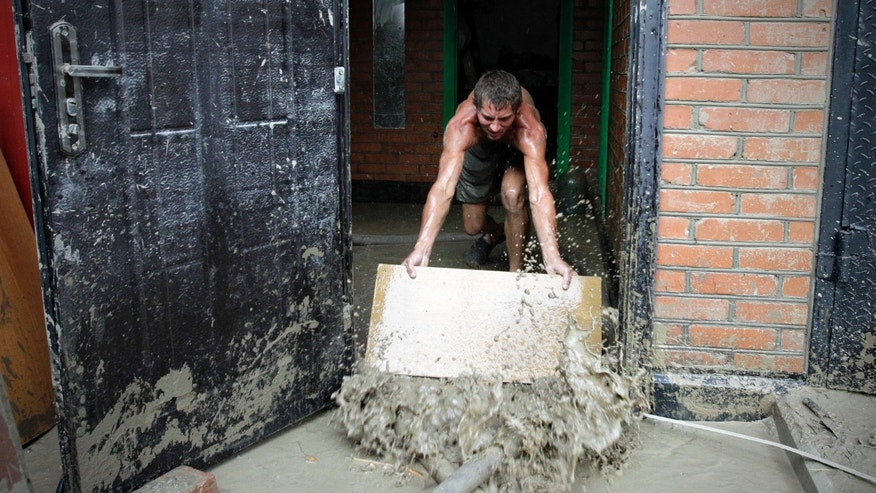 A man pushes water from his house in Krimsk, about 1,200 kilometers (750 miles) south of Moscow, Sunday July 8, 2012. Intense flooding in the Black Sea region of southern Russia killed at least 150 people after torrential rains dropped nearly a foot of water, forcing many to scramble out of their beds for refuge in trees and on roofs, officials said Saturday. (AP Photo/Sergey Ponomarev)