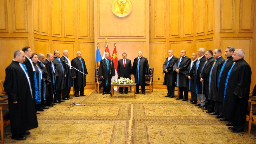 "In this image released by the Egyptian President, Egyptian President Mohammed Morsi, center left, stands with judges Farouk Sultan, second left, and Maher el-Beheri, center right, as he is sworn in at the Supreme Constitutional Court in Cairo, Egypt, Saturday, June 30, 2012. Islamist Mohammed Morsi promised a ""new Egypt"" and unwavering support to the powerful military as he took the oath of office Saturday to become the country's first freely elected president, succeeding Hosni Mubarak who was ousted 16 months ago. (AP Photo/Egyptian Presidency)"