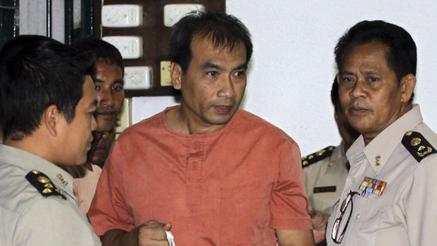 December 8, 2011: Joe Gordon, a Thai-born American, center, is escorted by correction officials at a criminal court in Bangkok, Thailand.