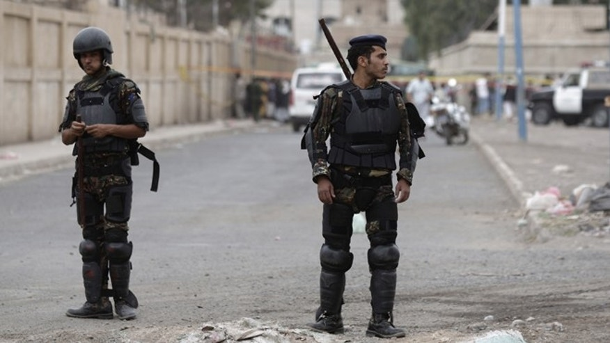 July 11, 2012: Yemeni soldiers stand guard at the site of a suicide bomb attack at a police academy in Sanaa, Yemen.