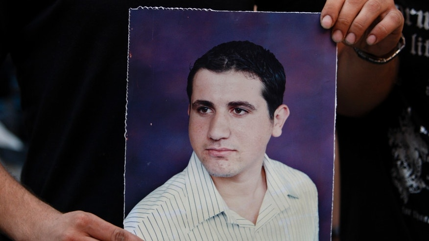 July 16, 2012: A Palestinian Christian holds a poster of Ramez Al-Amash, 25, who was allegedly kidnapped, during a rally for his release, at a Greek Orthodox church in Gaza City.