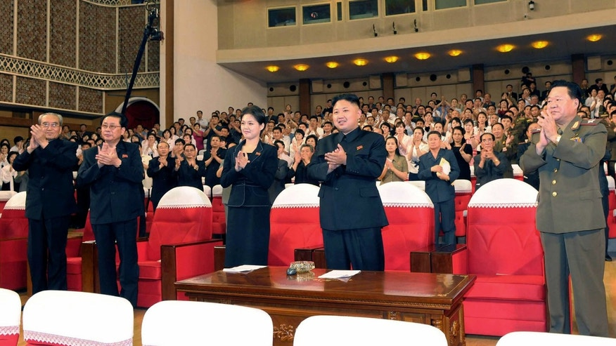In this photo released by the Korean Central News Agency (KCNA) and distributed in Tokyo by the Korea News Service on Monday, July 9, 2012, North Korean leader Kim Jong Un, center right, and a woman clap with others as they watch performance by North Korea's new Moranbong band in Pyongyang, North Korea, Friday, July 6, 2012. The source did not identify the woman but South Korean media speculated that she could be Kims younger sister or wife. (AP Photo/Korean Central News Agency via Korea News Service) JAPAN OUT UNTIL 14 DAYS AFTER THE DAY OF TRANSMISSION