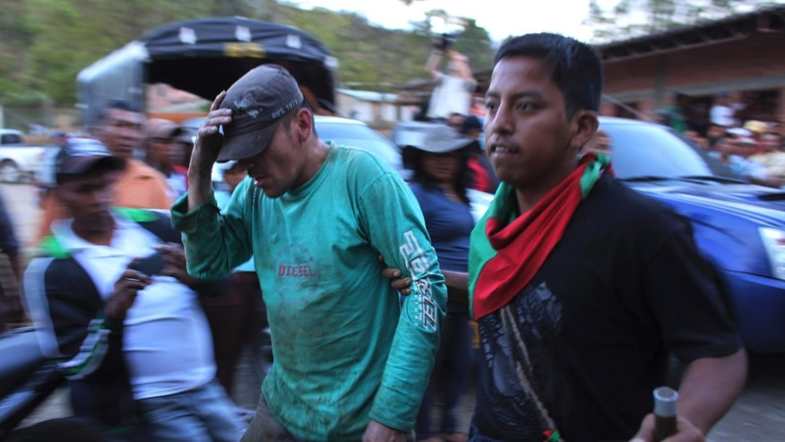 July 18, 2012: A member of the Nasa Indian Guard, right, escorts an alleged rebel in Toribio, Colombia.