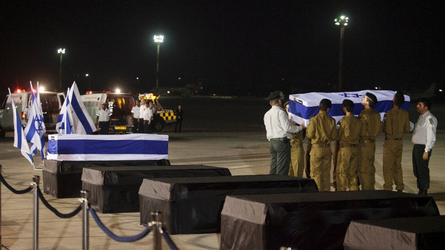 July 20, 2012: Israeli soldiers carry the coffins of people killed in a bombing in Bulgaria as the remains arrived back at an airport in Tel Aviv, Israel.