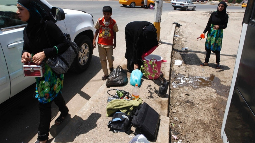 July 20. 2012: Iraqi refugees who have just returned from Syria unload their luggage from a bus in the Mansour neighborhood of Baghdad, Iraq.
