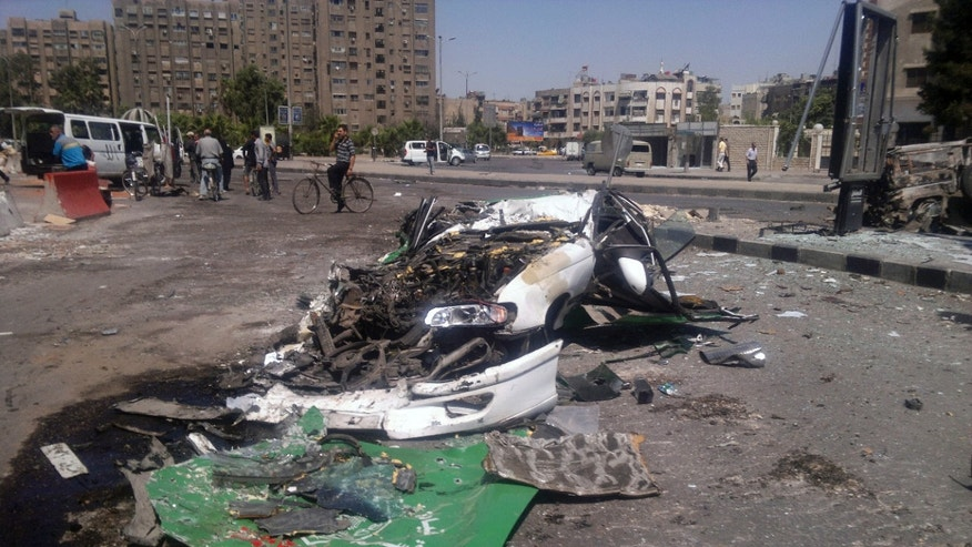 July 21, 2012: This citizen journalist image shows a destroyed car on a street damaged by tank treads after fighting between rebels and Syrian troops in the Yarmouk camp for Palestinian refugees in south Damascus, Syria.