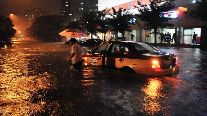 July 21, 2012: A taxi driver walks away after his car was stranded in a flooded street following a heavy rain in Beijing.