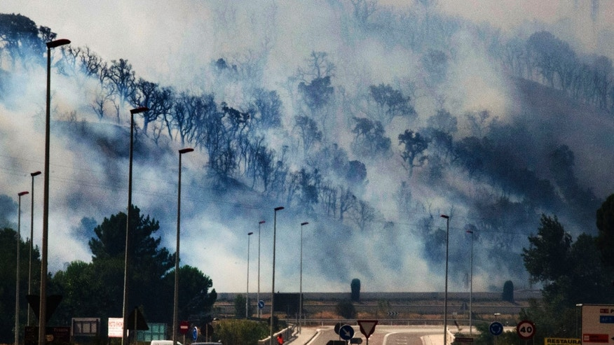 July 22, 2012: Smoke clings to the forest as flames burn the forest near the highway in La Jonquera, Spain, near the border with France. The regional officials said wildfires have burned almost 17,297 acres of forest.