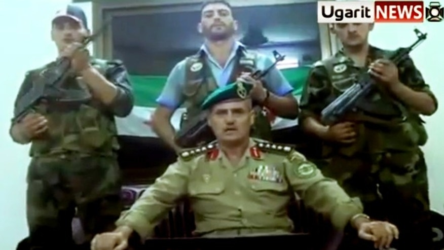 "This Saturday July 21, 2012 image made from amateur video released by the Ugarit News and accessed Sunday, July 22, 2012, purports to show Syrian Brig. Gen. Abdul-Nasser Farzat, center front, from the Aleppo Academy for Military Engineering, and warrant officer Ziad Ahmad Khodr from Criminal Security, center back, announcing their defection to the Free Syrian Army in Aleppo, Syria. In the video Farzat says, ""I have joined the Free Syrian Army, the army of heroes that is defending the nation."""