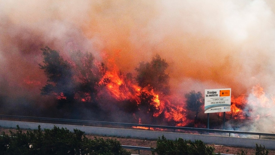 July 22, 2012: Flames ravage the forest near the highway in La Jonquera, near the border with France, Spain, Sunday.