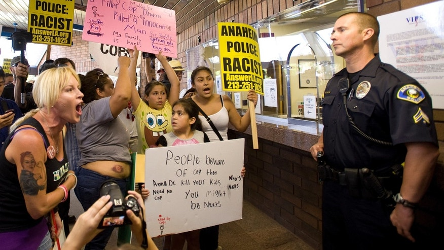 Activist Marlena Carrillo shouts at police inside the Anaheim Police Department Sunday July 22, 2012 where a press conference took place in response to the officer involved killing of Manuel Diaz Saturday.  (AP Photo/The Orange County Register, Mindy Schauer)