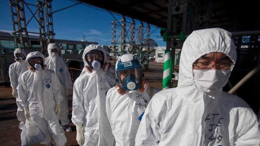 Nov. 12, 2011: In this file photo, workers in protective suits and masks wait to enter the emergency operation center at the crippled Fukushima Dai-ichi nuclear power station in Okuma, Japan.