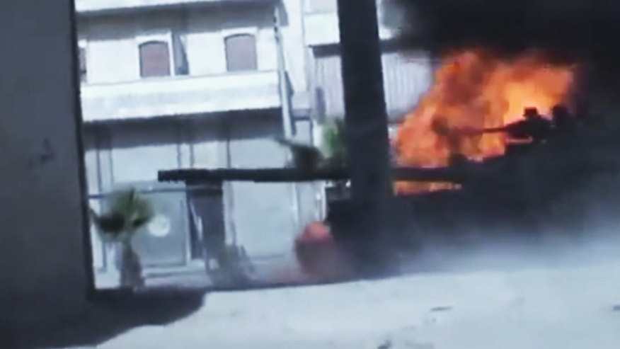 July 23, 2012:  In this image made from amateur video released by the Ugarit News, Syrian government troops are seen on a military tank as it catches on fire during clashes with Free Syrian Army soldiers in Aleppo, Syria.