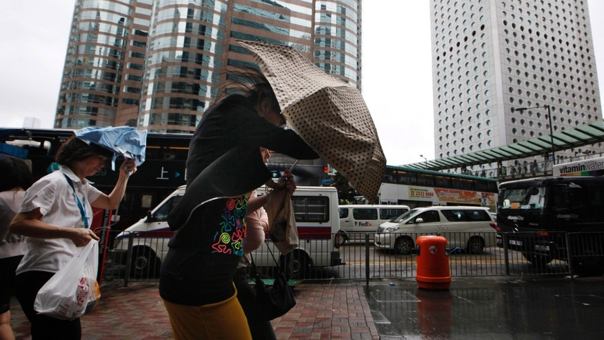 July 23, 2012  Pedestrians brave the strong winds in Central, the business center in Hong Kong.