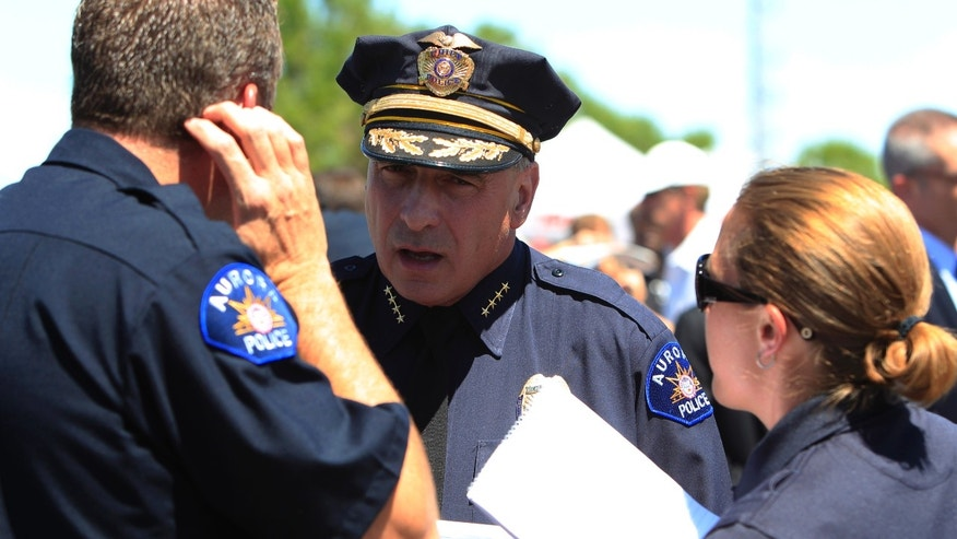 Aurora, Colo., Police Department Chief Daniel Oates, center, confers with officers before a news conference at the Century 16 Theater east of the Aurora Mall in Aurora, Colo., on Friday, July 20, 2012.