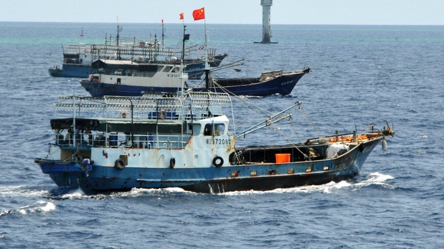 July 18, 2012: In this photo released by China's Xinhua, Chinese fishing vessels sail past a beacon of Zhubi Reef of the Spratly islands in South China Sea.