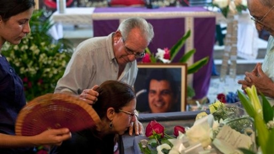 Ofelia Acevedo, second from left, widow of the late Cuban activist Oswaldo Paya, is comforted by an unidentified man in front of the coffin containing her husband's body during a funeral mass in Havana, Cuba, Monday, July 23, 2012. Paya, who spent decades speaking out against the communist government of Fidel and Raul Castro and became one of the most powerful voices of dissent against their half-century rule, died Sunday in a car crash. He was 60. (AP Photo/Ramon Espinosa)