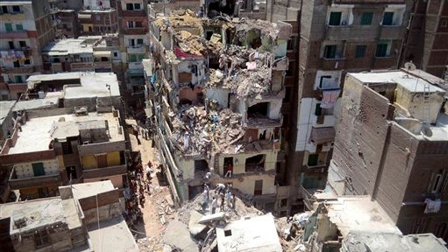 July 15, 2012: In this file photograph, rescue workers look for survivors buried under debris of damaged buildings following the collapse of an 11-story building under construction onto three adjacent buildings that killed at least 10 people in the Gomrouk neighborhood of Alexandria, Egypt.