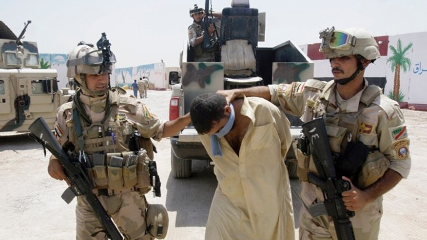 July 25, 2012: Iraqi army soldiers bring in a blindfolded and handcuffed suspected Al Qaeda member to detention centers in an Iraqi army base in Baghdad, Iraq.