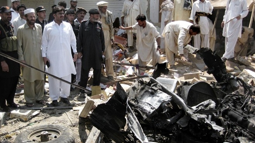 FILE: July 26, 2012: Pakistani investigators look for evidence at the site of a bomb blast in the Pakistani tribal area of Khar, Bajur.