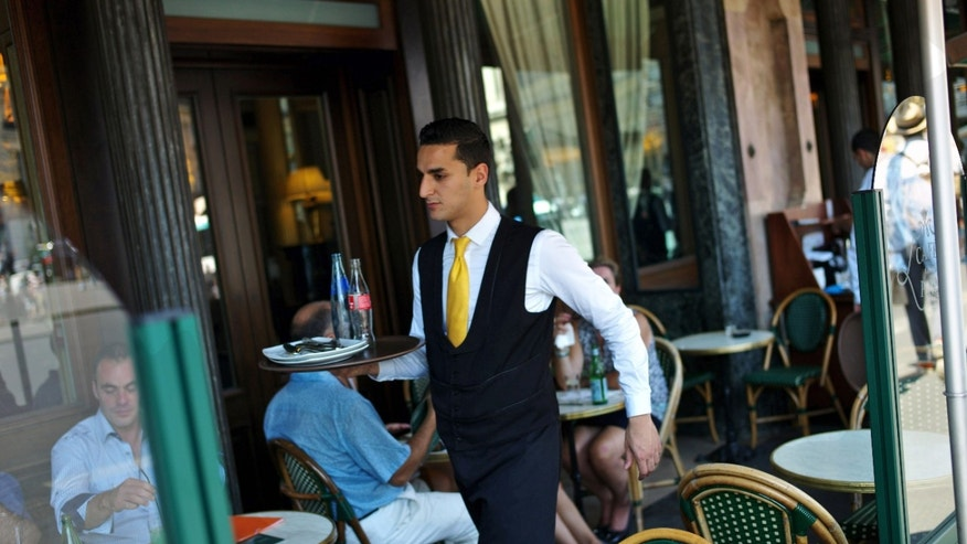 "This Thursday, July 26, 2012 photo shows a waiter working at a cafe terrace in Paris. France, a country famed for its arrogant waiters and proud taxi drivers, is finally getting fed up with rudeness. Polling trends show that impoliteness is now topping lists on causes of stress for the French, who lament that people don't say ""thank you"" anymore. Paris public transport is weighing in, with a summer-long publicity campaign poking fun at gallic incivility.  (AP Photo/Thibault Camus)"