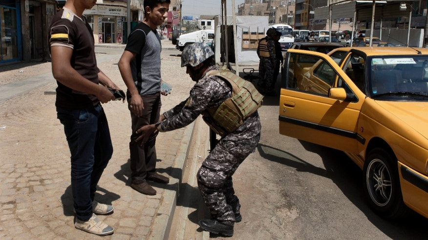 July 15, 2012: An Iraqi police officer searches people at a checkpoint in central Baghdad, Iraq.