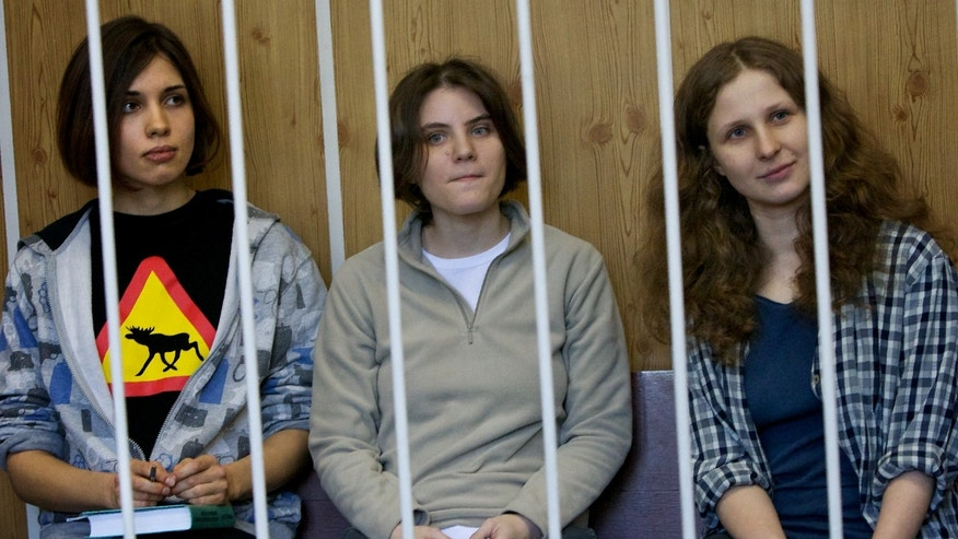 "From left, Nadezhda Tolokonnikova, Maria Alekhina, Yekaterina Samutsevich members of feminist punk group Pussy Riot sit behind bars at  a court room in Moscow, Russia, Monday, July 23, 2012.The trial of feminist punk rockers who chanted a ""punk prayer"" against President Vladimir Putin from a pulpit inside Russia's largest cathedral started in Moscow on Friday amid controversy over the prank that divided devout believers, Kremlin critics and ordinary Russians. (AP Photo/Alexander Zemlianichenko)"