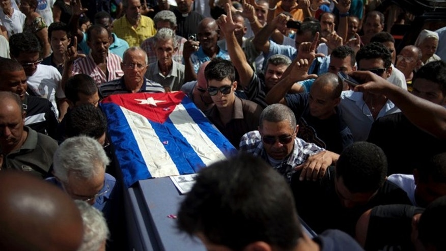 Friends and family of the late Cuban activist Oswaldo Paya carry his flag draped coffin during his burial at a cemetery in Havana, Cuba, Tuesday, July 24, 2012. Paya, 60, gained international fame as the lead organizer of the Varela Project, a signature-gathering drive asking authorities for a referendum on guaranteeing rights such as freedom of speech and assembly. The initiative launched a decade ago was seen as the biggest nonviolent campaign to change the system Fidel Castro established after the 1959 Cuban revolution. Paya died on Sunday, July 22, 2012 in a car crash.  (AP Photo/Ramon Espinosa)