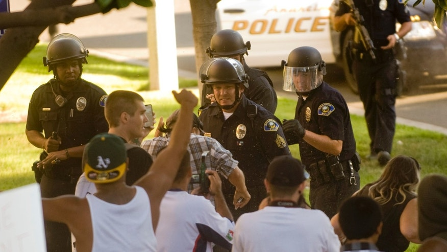 A group of Anaheim police officers try to hold back a crowd of protesters as they wait reinforcements Tuesday afternoon July 25, 2012, in Anaheim, Calif. (AP)