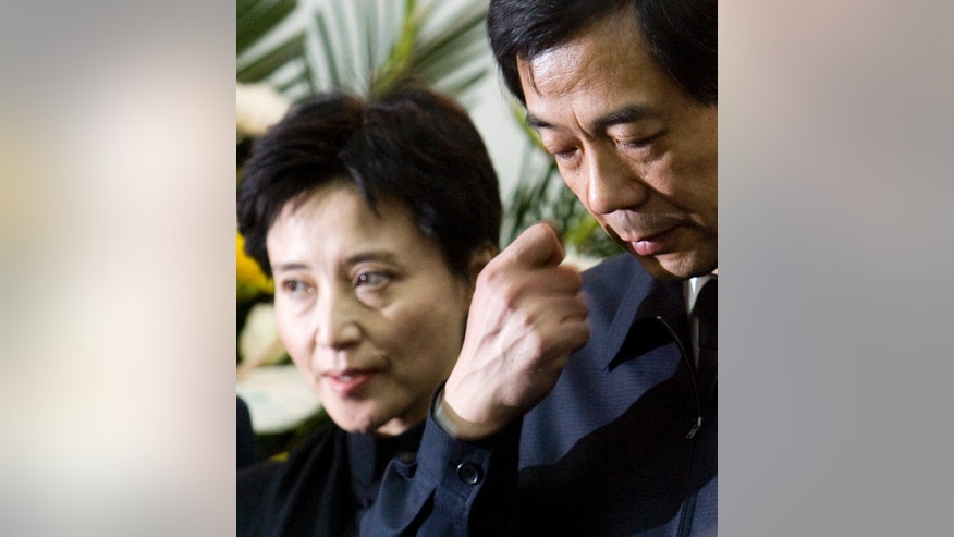 FILE - In this Jan. 17, 2007 file photo, Bo Xilai, right, then China's Minister of Commerce, and his wife Gu Kailai, left, attend a memorial ceremony for Bo's father Bo Yibo, a late revolutionary leader considered one of communist China's founding fathers, at a military hospital in Beijing. Gu could go on trial in the coming days, after being formally charged with the murder of a British businessman who was a close associate of the Bo family. The murder is at the center of a messy political scandal that has highlighted divisions in the Chinese leadership ahead of a once-a-decade political transition in 2012. (AP Photo/Alexander F. Yuan, File)