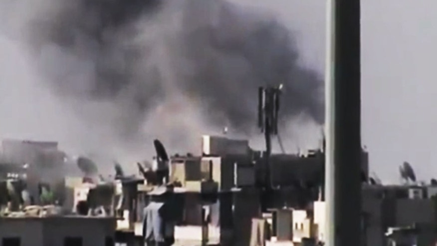 This image made from amateur video released by the Ugarit News and accessed Tuesday, July 31, 2012, purports to show black smoke rising from buildings in Aleppo, Syria.
