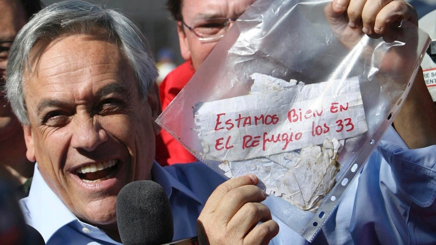 "President Sebastian Pinera holds up a plastic bag containing a message,from miners trapped in a collapsed mine that reads in Spanish ""We are ok in the refuge, the 33 miners"" in Copiapo, Chile. (AP Photo/Hector Retamal, File)"