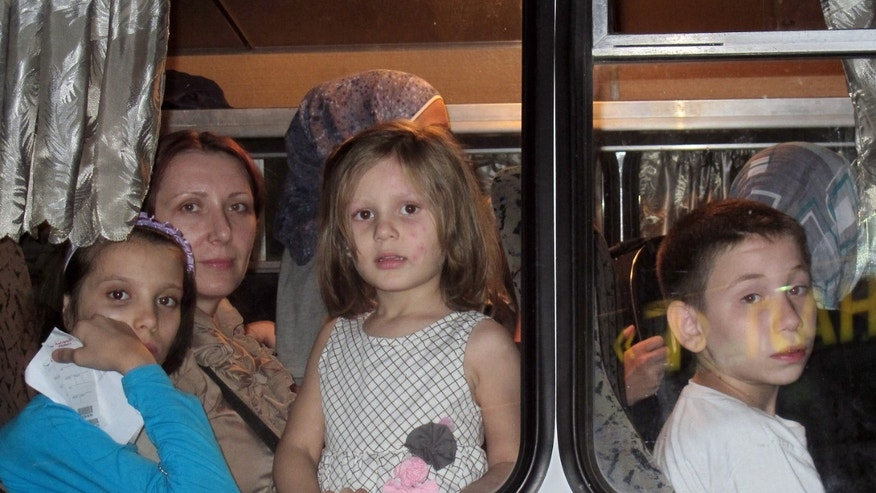 Aug. 1, 2012: Women and their children look out of the window in a Ukrainian Emergency Situations Ministry's bus after arriving at Kiev's Boryspil airport from Syria.